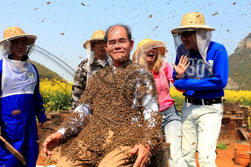 Recouvert d'abeilles, Monsieur Yang Chuan essaye de sourire à la foule assemblée pendant que les présentateurs de CCTV4 continuent le programme avec beaucoup de courage.///Covered in bees, Mister Yang Chuan tries to smile to the gathered crowd while the anchormen from CCTV4 continue the program with a lot of courage.