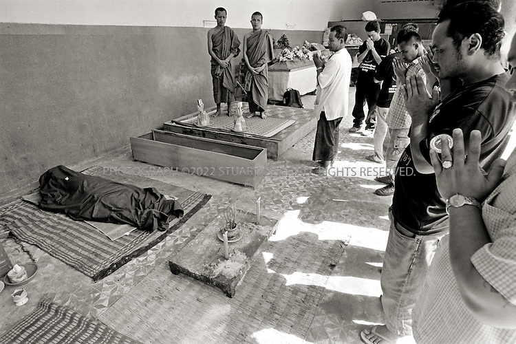 12/8/2007--Phnom Penh, Cambodia..Deportees, including Hin Roatnak, aka Cobra (right),pray in front of the coffin of Var Chan, aka. Chan, aka. Rascal, who committed suicide 3 days before at the age of 34, is cremated. Chan had been in Cambodia for a year since his deportation from the United States...©2007 Stuart Isett. All rights reserved