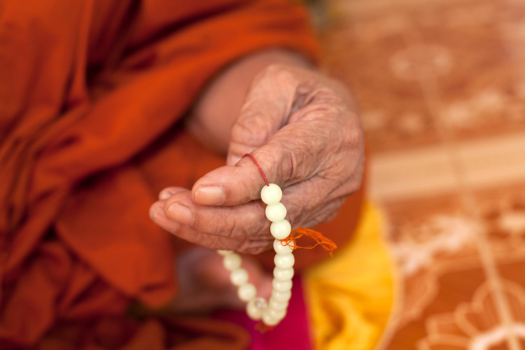 Detail of hand with prayer beads of an 80-year-old blind monk lives in a temple in a village near Battambang, Cambodia. <br /> <br /> Photos &copy; Dennis Drenner 2013.