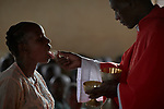 Father Zacharia Osman serves the Eucharist to a woman during a Catholic Mass in Lugi, a village in the Nuba Mountains of Sudan. The area is controlled by the Sudan People's Liberation Movement-North, and frequently attacked by the military of Sudan.