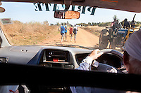 Renato Canova coaches elite Kenyan runners inthe high altitude town of Iten. Here he monitors times from his pace car during a training run outside Iten.