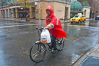 New York, NY -  29 Oct 2012 A man delivering food on an electric bicycle during Hurricane Sandy.