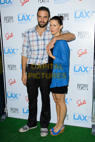 guest &amp; Sarah Jane Potts<br /> Next Stop LAX, Launch Party, London, England.<br /> 9th July 2013<br /> full length black trousers blue check shirt dress arm over shoulder shirt beard facial hair<br /> CAP/CJ<br /> &copy;Chris Joseph/Capital Pictures