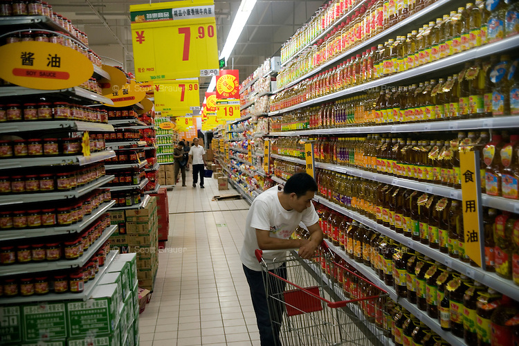 A man looks at the selection of cooking oils in a hypermarket in Nanjing, Jiangsu, China.