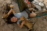 Five year old Ine Ahua, a Waorani (Huaroni) boy, plays with his pet puppies at his home.