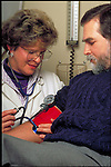 nurse checks blood pressure of male patient