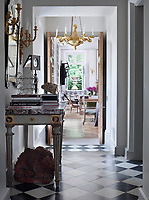 A view along the hallway, with its black and white, check pattern marble flooring to the family room beyond.