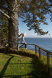 USA, California, Big Sur, Esalen, woman sits on the fence near the Farm House and enjoys the sun and the views of the Pacific, the Esalen Institute