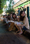 Visitors enjoy a take-out meal while sitting on the curb at the weekly night market in Garapan, Saipan.  .Robert Gilhooly Photo