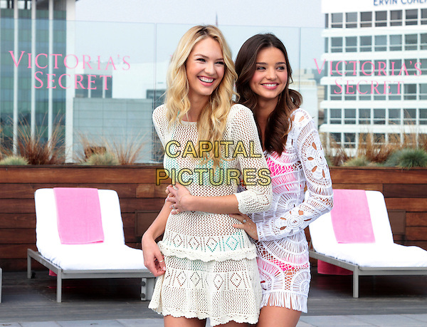 Candice Swanepoel, Miranda Kerr.Victoria's Secret Celebrates its 2012 Swim Collection held at the Thompson Hotel in Beverly Hills, Beverly Hills, California, 29th March 2012..half length models  white crochet dress pink turquoise bikini smiling .CAP/ADM/SLP/JO.©James Orken/Starlitepics/AdMedia/Capital Pictures.
