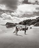 NICARAGUA, San Juan Del Sur, srufers walking on Maderas Beach (B&W)
