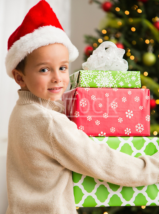 Boy (6-7) holding stack of Christmas presents