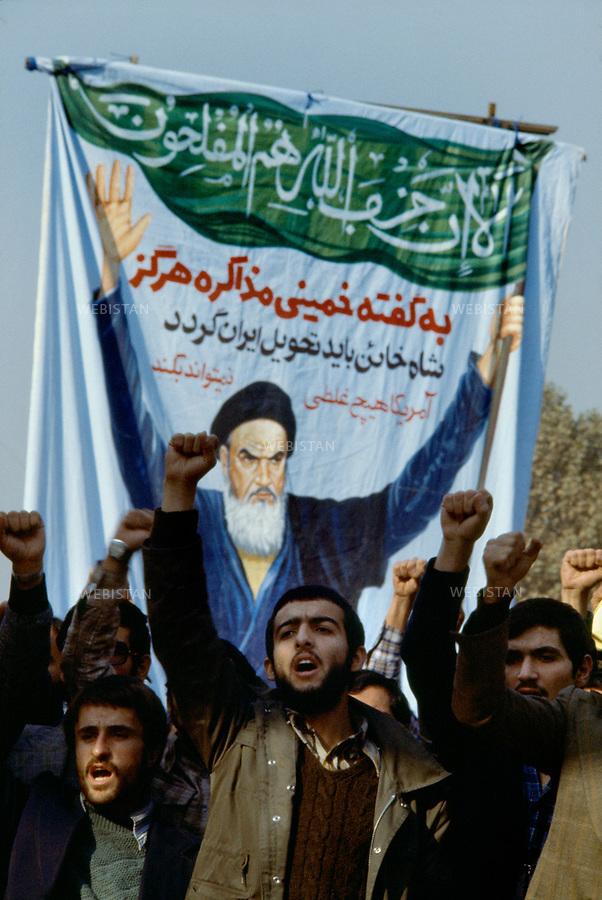 TEHRAN, IRAN - NOVEMBER 1979: Inside of the occupied U.S. embassy, a group of protesters shout slogans in front of painting of the religious leader of the 1979 Iranian revolution; Ruhollah Musavi Khomeini, with the written slogan: &quot; No negotiation, the traitor shah must be returned to Iran, America can not do anything.&quot; The hostage crisis was a diplomatic crisis between Iran and the United States where 52 U.S. diplomats were held hostage for 444 days from November 4, 1979 to January 20, 1981, after a group of Islamist students took over the American embassy in support of the Iranian revolution. (Photo by Reza/Webistan).<br /> T&eacute;h&eacute;ran, Iran - Novembre 1979. A l'int&eacute;rieur de l'ambassade des Etats Unis, occup&eacute;e, un groupe de manifestants brandit des photos et des peintures du chef religieux de la r&eacute;volution iranienne de 1979 : Ruhollah Musavi Khomeini, avec un slogan &eacute;crit sur la banderole :&quot;pas de n&eacute;gotiation. Le shah est un traitre et doit retourner en Iran. L'Am&eacute;rique ne peut pas faire n'importe quoi.&quot;.  La crise des otages &agrave; T&eacute;h&eacute;ran fut une crise diplomatique entre l'Iran et les Etats Unies durant laquelle 52 diplomates am&eacute;ricains furent pris en otage par un groupe d'&eacute;tudiants islamistes apr&egrave;s qu'ils se soient empar&eacute;s de  l'ambassade am&eacute;ricaine dans le cadre de leur soutien &agrave; la r&eacute;volution islamique. Les otages rest&egrave;rent  prisonniers pendant 444 jours du 4 novembre 1979 au 20 janvier 1981 (Photo de Reza/Webistan).