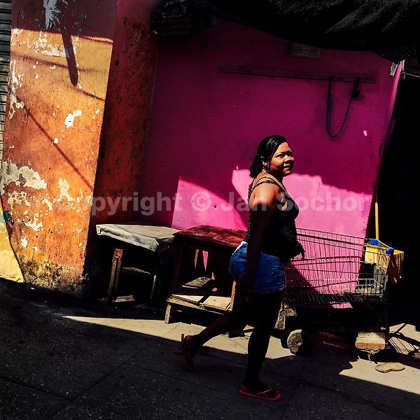 A Colombian woman walks along a customized supermarket cart parked at the market of Bazurto in Cartagena, Colombia, 13 April 2018.