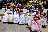 Itaparica Island, Brazil. Procession of women in full dresses with vases of flowers on their heads - washing the churches ceremony.