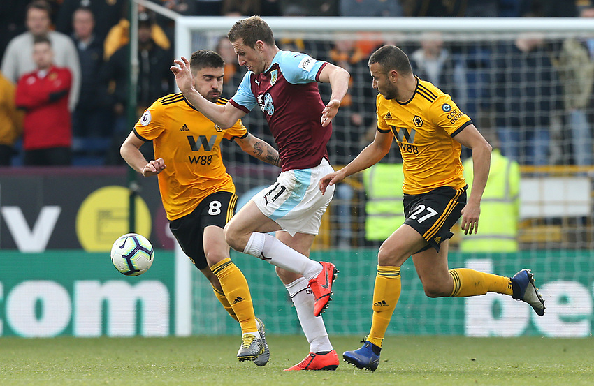 Burnley's Chris Wood vies for possession with Wolverhampton Wanderers' Ruben Neves (left) and Romain Saiss<br /> <br /> Photographer Rich Linley/CameraSport<br /> <br /> The Premier League - Burnley v Wolverhampton Wanderers - Saturday 30th March 2019 - Turf Moor - Burnley<br /> <br /> World Copyright © 2019 CameraSport. All rights reserved. 43 Linden Ave. Countesthorpe. Leicester. England. LE8 5PG - Tel: +44 (0) 116 277 4147 - admin@camerasport.com - www.camerasport.com