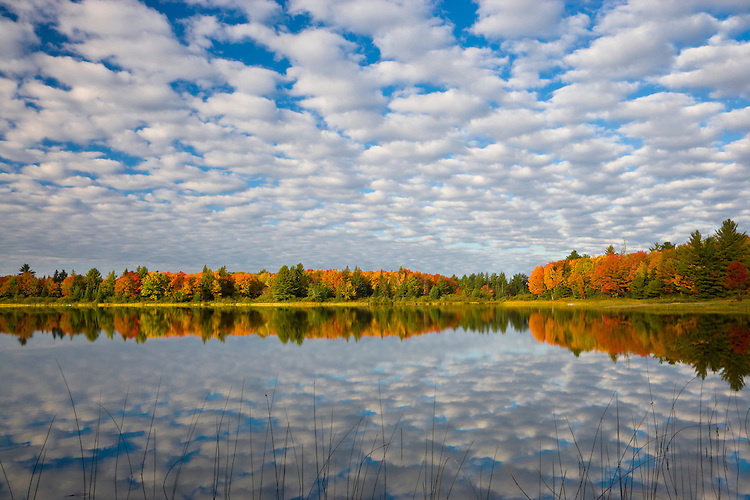 Sunrise light on cloud and fall color reflections on Otter Lake in the Hiawatha National Forest, MI