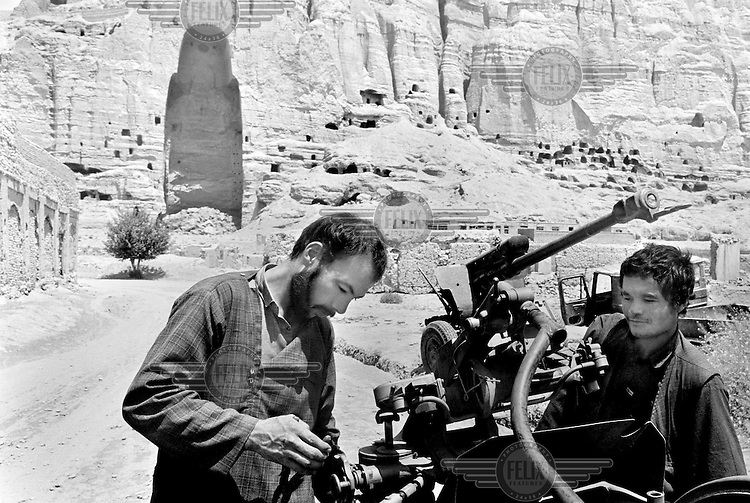 Two Afghan militiamen work on repairing artillery pieces near one of the destroyed Buddha statues in Bamiyan, Afghanistan on Tuesday, June 25, 2002. The two Buddha statues are thought to have been carved into the sandstone cliffs of Bamiyan in the third century A.D. At 53 meters (175 feet) and 36 meters (120 feet), the statues were the tallest standing Buddhas in the world.