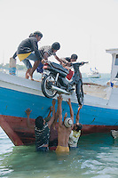 A group of Timorese men loads a motorcycle onto a boat in Dili harbor for a trip to Atauro Island, Timor-Leste (East Timor)