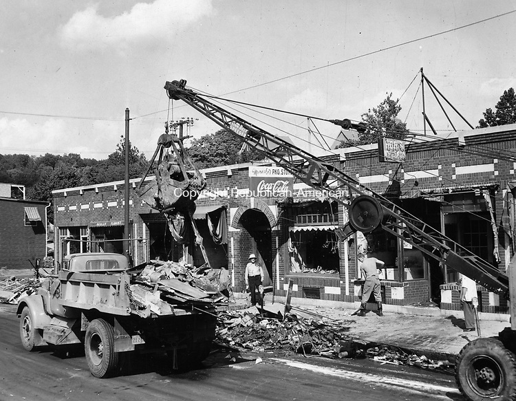 This is a familiar sight here these days as clean-up operations get into full swing to get out from under debris left by last week's flood waters. State Highway Department truck and equipment is shown working on North Main Street here. 25 August 1955.