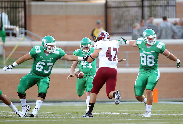 Denton, TX - SEPTEMBER 22: Offensive linesman Nicolas Summerfield #63 of the North Texas Mean and tight end Tanner Smith #88 block linebacker Eli Canton #47 of the Troy Trojans as Will Atterberry #41 punts the ball at University of North Texas Apogee Stadium in Denton on September 22, 2012 in Denton, Texas. (Photo by Rick Yeatts)