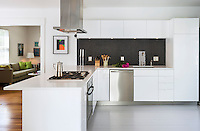 A modern, spacious white kitchen with a peninsula unit. A stainless steel extractor fan is set over a gas hob set in the worktop. The splashback is of grey mosaic tiles.