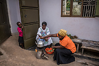 Uganda, Bujuuko. Jalia Musoke runs a tree farm and sewing business. She is busy with work and chores and uses a BioLite wood cook stove that she feels is faster than a regular cookstove. At home using her cookstove. With Hajara Namboozi, , a Brightlife senior sales agent.
