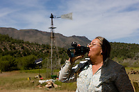 Maryann Pratt takes a drink of water while working on her rural ranch. (Pat Shannahan/ The Arizona Republic)