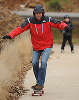 NWA Media/ANDY SHUPE - Giovanni Petris of Fayetteville smiles as he rides a skateboard while his son, Matteo, 7, right, laughs Wednesday, Dec. 31, 2014, in Wilson Park in Fayetteville. Matteo received the skateboard as a Christmas gift and was racing his father on a gentle downhill.
