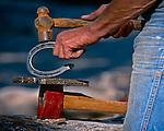 Cowboy shaping a mule shoe, Sierra Nevada, California