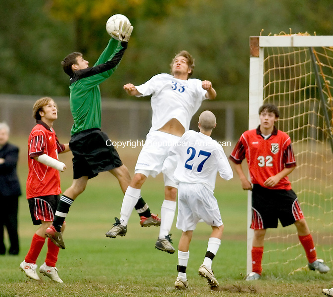 WOODBURY, CT-- 09 OCTOBER 2007--100907JS07-Northwestern goal keeper Russell Dougan goes up to take control of the ball on a corner kick intended for Nonnewaug's David Martland (33) during their game Tuesday at Nonnewaug High School. <br /> Jim Shannon / Republican-American