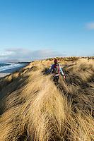 Woman walks through coastal dune grass at west beach, Berneray, Outer Hebrides, Scotland