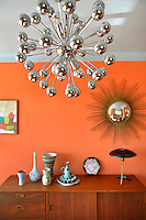 A chrome Sputnik pendant light adds to the retro 1950s style of the dining room
