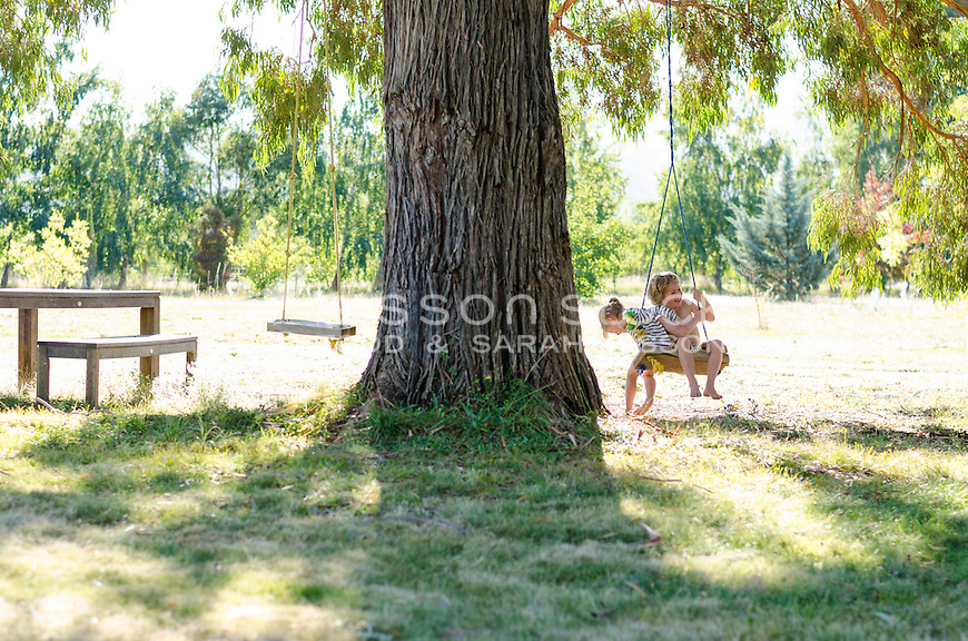 Young boy and young girl smiling and sharing a rope swing, New Zealand - stock photo, canvas, fine art print