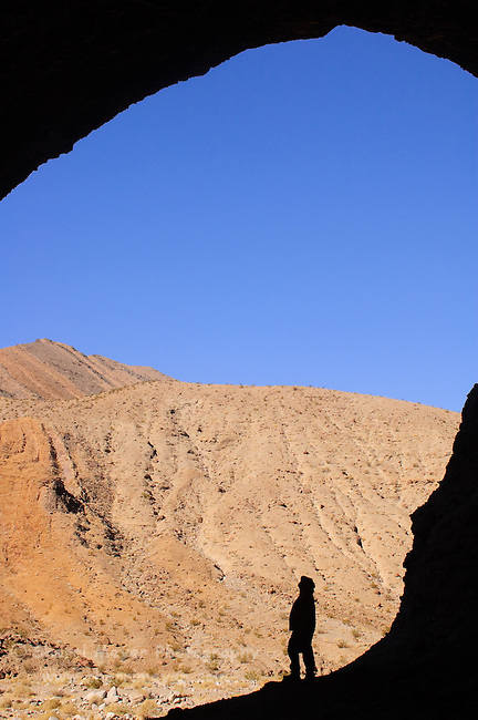 Man exploring a cave in Cottonwood Canyon, Death Valley National Park, California