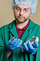Dr. Trey Howell using a glucometer to measure blood glucose levels in a mouse for a research study on diabetes.