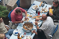 A group (likely an extended family) enjoys an outdoor lunch of chicken stewed with root vegetables and rose wine during the festival of Aigues-Mortes.