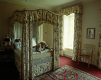 This grand child's bedroom is furnished with a small four-poster bed with bed hangings and matching curtains in an antique chintz