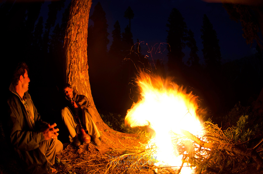 Bakarwal gypsy men smoking traditional hookha hubbly bubbly by campfire, Western Himalayan Mountains, Kashmir, India..