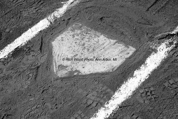 B&W closeup of baseball home plate with batter's box lines and dirt.