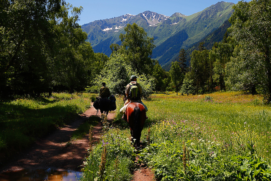 Russia, Caucasus, Teberdinsky Biosphere reserve, riding through flower meadows in the Arkhyz valley in the western part of the reserve.<br /> Model release form 2 and 3.