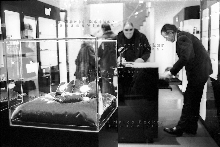 Milano, via Montenapoleone. Clienti e commesso in una gioielleria con degli orologi sotto teca in vetrina --- Milan, Montenapoleone street. Customers and salesperson in a jewelry store with watches on display