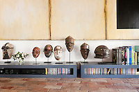 In the living room a low sideboard houses the stereo and a collection of African masks