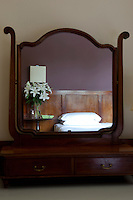 A double bed with a wood panelled headboard is reflected in a dressing table mirror