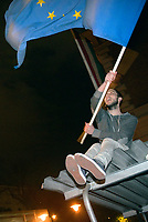 UNGARN, 11.04.2017, Budapest - VIII. Bezirk. Demonstration gegen den Beschluss der Fidesz-Regierung, den Weiterbetrieb der von George Soros finanzierten und fuer ihre Liberalitaet und Weltoffenheit bekannte. Zentraleuropaeishcen Universitaet CEU legislativ zu verunmoeglichen. -Ende einer Spontandemonstration am alten Rundfunkgebaeude auf dem Pollack Mih&aacute;ly Platz. Man fordert Pressefreiheit und hisst die Europaflagge, das Symbol der Opposition. Schwere Polizeikraefte sichern das Gebaeude. Hier begann der Volksaufstand von 1956. | Demonstration against the Fidesz government's decision to legally make it impossible to further uphold the Central European University, financed by George Soros and known for its liberal and cosmopolitan spirit. -A spontaneous demonstration finishing at the old radio central on Pollack Mihaly square. They demand press freedom and manage to put up the EU flag, the symbol of opposition. Heavy police forces securing the building. This was one of the places where the 1956 uprising began.<br /> &copy; Martin Fejer/EST&amp;OST