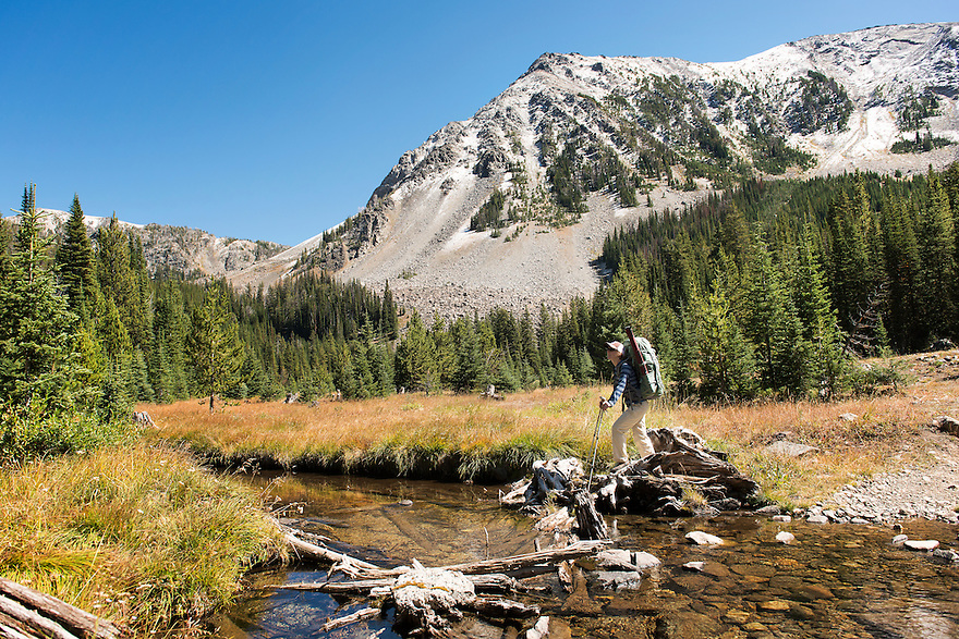 Christine Marozick, of Bozeman, Montana, crosses a creek below Sunrise Peak in the Tobacco Root Mountains south of Twin Bridges, Montana.