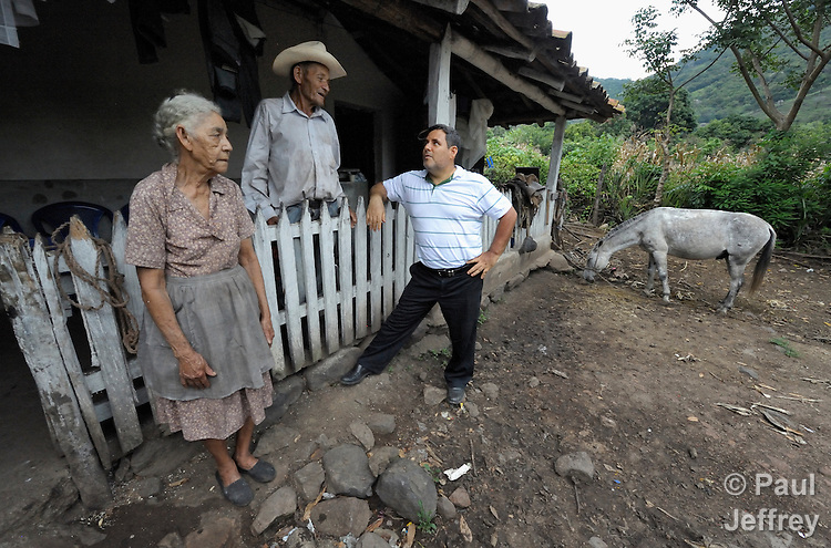 The Rev. Juan Guerrero (right), a native of Colombia, is a United Methodist missionary and superintendent of the church's mission in Honduras. Here he visits with Maria Luisa Salinas and her husband Teofilo Rodriguez at their home in the rural village of Quisgualagua.