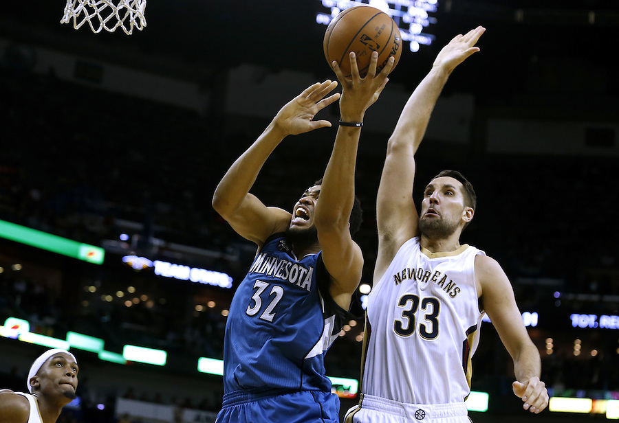 Minnesota Timberwolves center Karl-Anthony Towns (32) drives past New Orleans Pelicans forward Ryan Anderson (33) during the second half of an NBA basketball game Saturday, Feb. 27, 2016, in New Orleans. The Timberwolves won 112-110. (AP Photo/Jonathan Bachman)