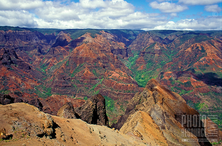 The vast multicolored vista of Waimea Canyon on the island of Kauai with white fluffy clouds on the horizon.