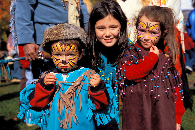Traditionally dressed  family of three children ages 9, 4 and 2 years old with painted faces at pow wow festival